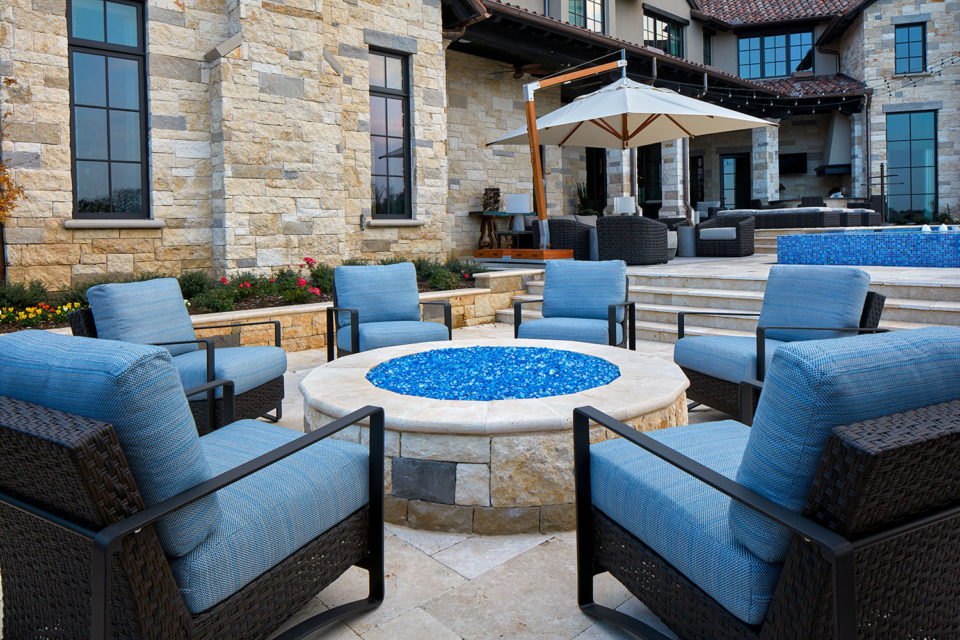 Backyard Stone Fire Pit With Woven, Upholstered Arm Chairs