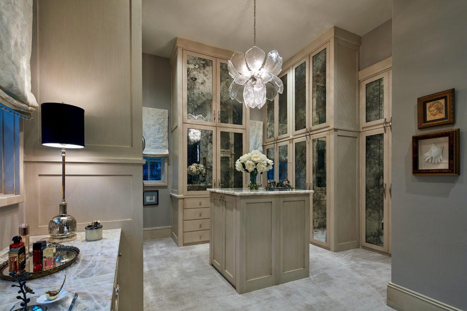 Expansive Woman's Closet with Vanity and Glass Front Custom Cabinets