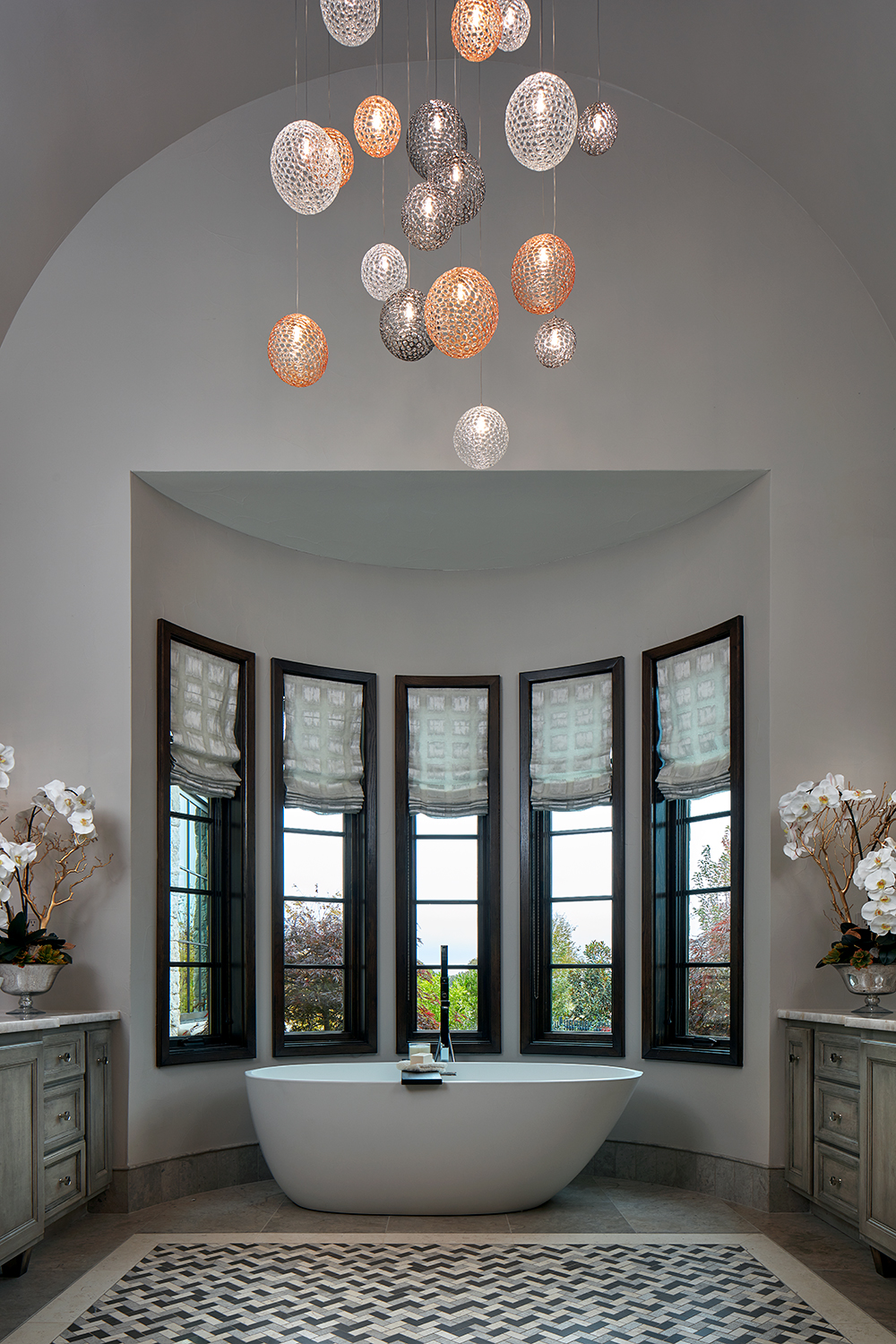 luxurious master bath with custom chandelier and white soaking tub