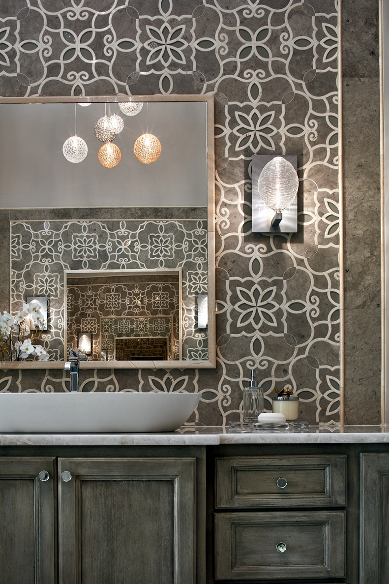 The intricate pattern of the backsplash is offset by the subdued mirror, vessel sink, sconces and cabinets.