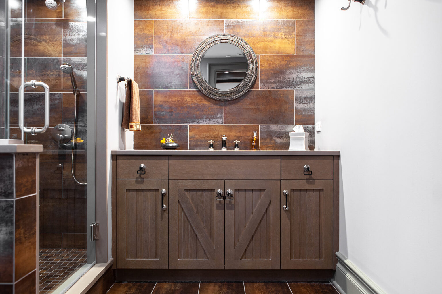dark wood vanity with multi-colored tile backsplash in orange and rust tones
