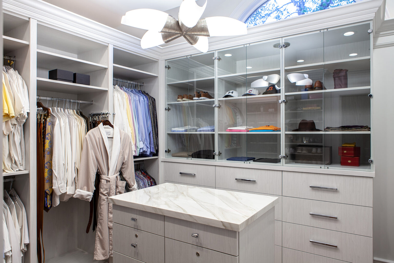 custom closet with off white cabinetry and glass doors