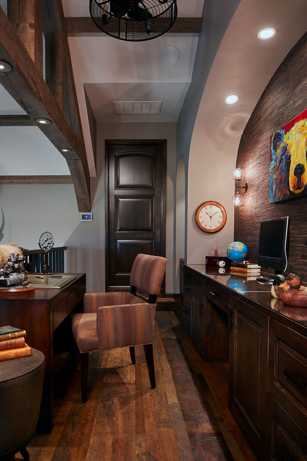 The husband's spacious study features a variety of wood tones and finishes.