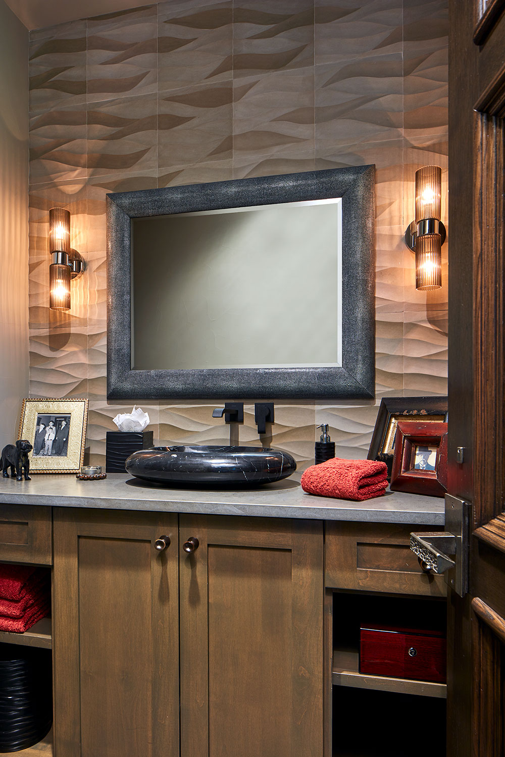 Like waves gently flowing across a pond, this sandstone tile backspalsh introduces motion and energy to the powder room in the husband's study/entertainment room.